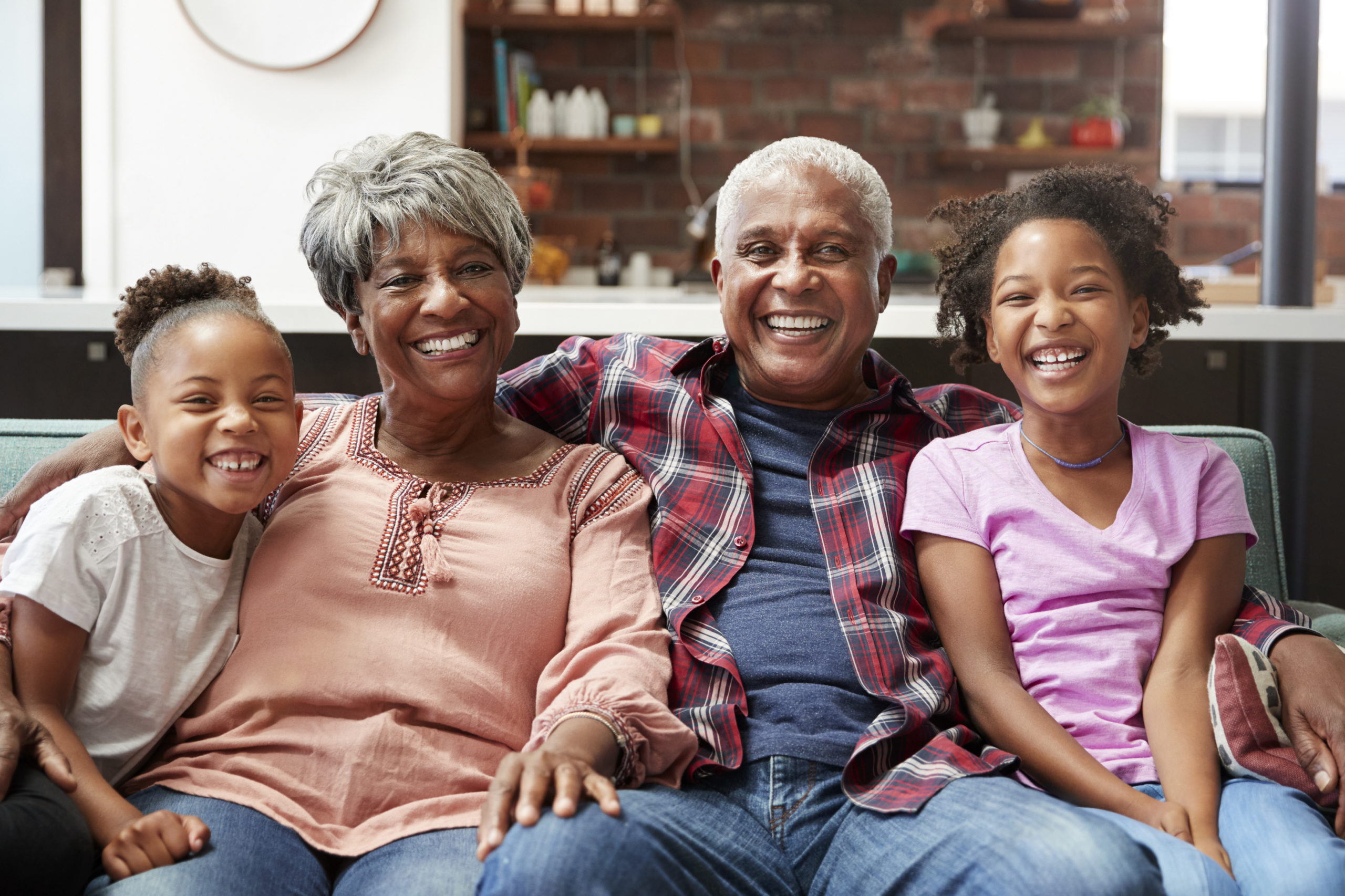 Portrait Of Grandparents Sitting On Sofa At Home With Granddaughters